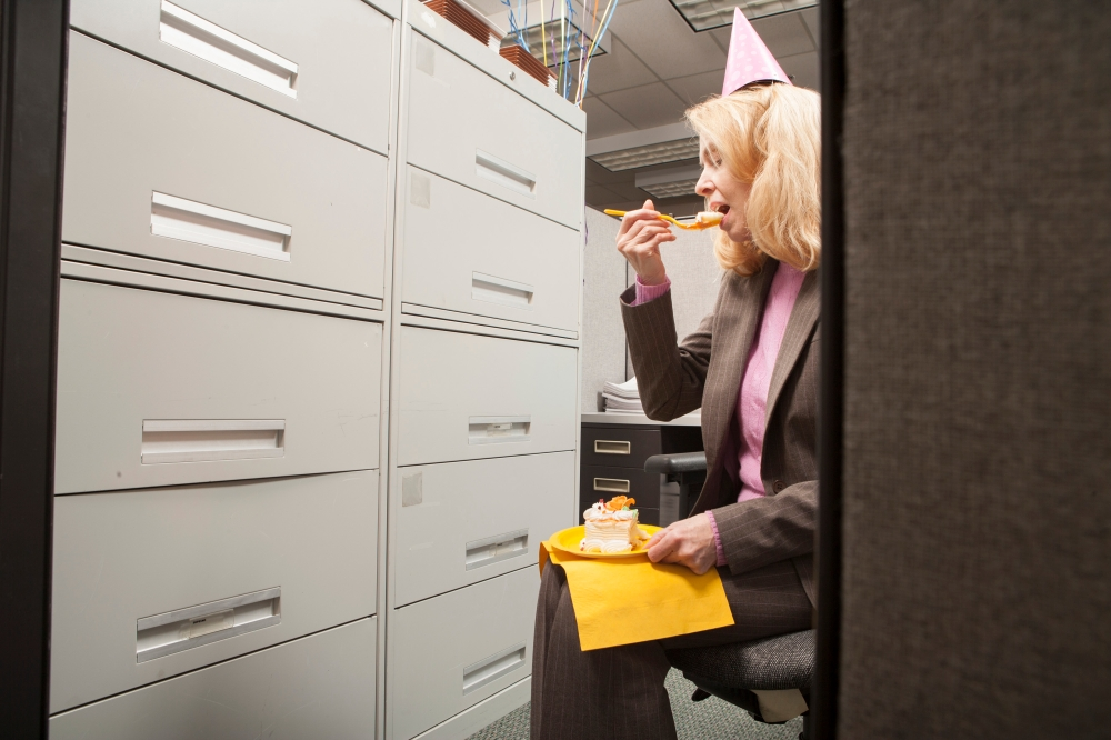 Business person eating birthday cake in cubicle Birthday at Work Office